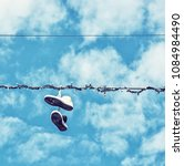 sneakers hanging on the power... | Shutterstock . vector #1084984490