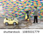 happy child washes yellow toy... | Shutterstock . vector #1085031779