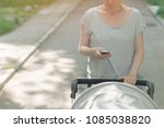 mother pushing baby stroller... | Shutterstock . vector #1085038820