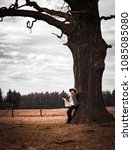 Small photo of Rural scene with woman in hat with map under old lonely tree, melancholic autumn mood