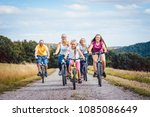 family riding their bicycles on ... | Shutterstock . vector #1085086649