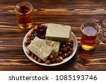Small photo of Tasty halva with tea, nuts, dried fruits on wooden table