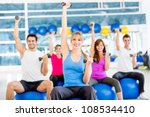 Group of people working out at the gym - stock photo