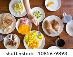 Small photo of Hands of a woman and kids having a healthy delicious breakfast table with cheese, toasted bread, croissants, pastry, scaramble eggs, orange and mango