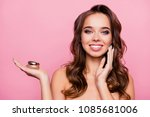Small photo of Concept of using moisturizing night cream - beautiful cute pretty charming woman propose a jar of injection and applying it on her cheek bone, isolated on pink background