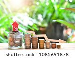 Small photo of house model on coins saving and decrease interest rates down for concept mortgage finance and home loan