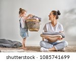 Stock photo beautiful young woman and child girl little helper are having fun and smiling while doing laundry 1085741699