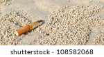Cigarette Butt In Sand. Litter...