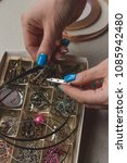 Small photo of Female hands holding accessories hardware for making stained window glass jewelry close up. Woman choosing details elements to create adornment bijouterie. Handmade craft industry