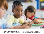 smiling african girl sitting at ... | Shutterstock . vector #1086016088