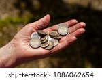 Small photo of Euro on hand. Many Euro coins on the hand of an Aten woman. Old age poverty in Germany. Background, poverty. Old woman