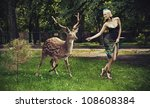 Young blonde lady running with deer - stock photo