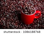 Whole roasted coffee beans and a coffee mug - stock photo