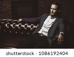 imposing young man sitting on a ...   Shutterstock . vector #1086192404