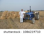 farmer standing with tractor | Shutterstock . vector #1086219710
