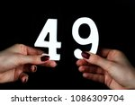 Small photo of On a black background, female hand with the number forty-nine.