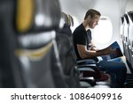 joyful man sits in the airplane ... | Shutterstock . vector #1086409916