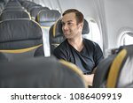 nice man sits in the airplane... | Shutterstock . vector #1086409919