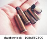 Small photo of Bullets on soft hand surfaces, symbols of danger and safety in life