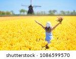 child in tulip flower field... | Shutterstock . vector #1086599570