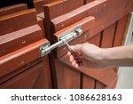 Woman Hand Pulling Latch Lock...
