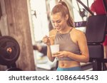 woman in gym eating healthy... | Shutterstock . vector #1086644543