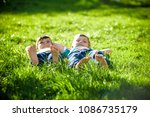 children laying on grass.... | Shutterstock . vector #1086735179