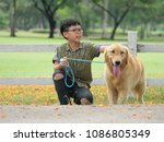 asian boy playing with puppy... | Shutterstock . vector #1086805349