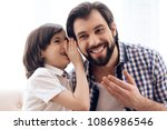 long haired son tells secret in ... | Shutterstock . vector #1086986546