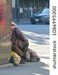 Small photo of The outline of a homeless person in tattered clothing sitting on a street corner with his worldly belongings.