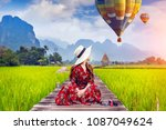 young woman sitting on wooden... | Shutterstock . vector #1087049624