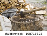 Rusty and used axe in wide old stump - stock photo