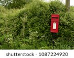 Red Postbox In Countryside Hedge