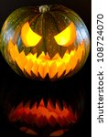 Halloween pumpkin with scary face with reflection - stock photo