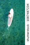 Small photo of Vouliagmeni, Attica / Greece - May 09 2018: Aerial photo of man practising paddle surfing or sup in clear waters of Vouliagmeni beach