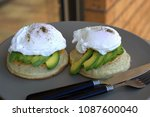 Small photo of Avocado and poached eggs on crumpets with jalapeno and cheddar sauce with sprinkle of salt and pepper. Close up and Selective focus on egg poach