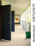 Small photo of Outside view of open door ways entrance to school classrooms from outside. High school education and study concept. strong depth and perspective, hallway portrait aspect.