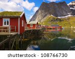Typical red rorbu fishing huts with sod roof on Lofoten islands in Norway reflecting in fjord - stock photo