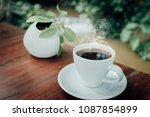 cup of coffee and small plant... | Shutterstock . vector #1087854899