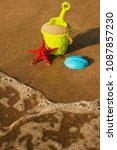 Small photo of starfish and children's pail with sand lie on the seashore