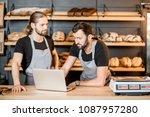 two handsome sellers in uniform ... | Shutterstock . vector #1087957280