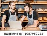 two handsome sellers in uniform ... | Shutterstock . vector #1087957283