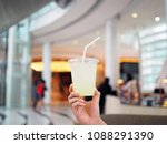 holds a plastic glass of iced... | Shutterstock . vector #1088291390