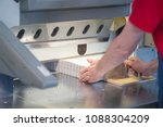Stock photo hands of worker working on cutter guillotine machine in a printing factory 1088304209