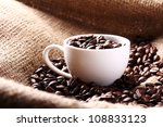 Cup Full Of Coffee Beans On Th...