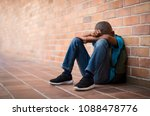 Small photo of Young boy sitting alone with sad feeling at school. Depressed african child abandoned in a corridor and leaning against brick wall. Bullying, discrimination and racism concept with copy space.