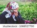 an elderly woman cries  wiping... | Shutterstock . vector #1088527700