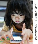 Small photo of Little Asian baby girl, 28 months old, using a cell phone - child's engagement with a mobile phone, in proper period of time, improving their technological intelligence, and learning awareness