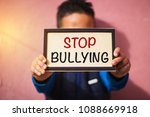 Small photo of Little boy holding cardboard with text stop bullying - victim children bullied abuse concept