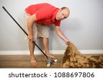 A Man Sweeping Something Under...
